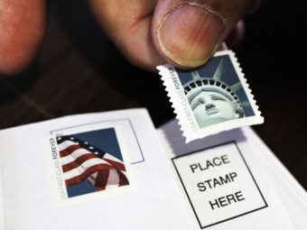 A customer places first-class stamps on envelopes at a U.S. Post Office in San Jose, Calif. It'll cost another 3 cents to send a first-class letter starting on Jan. 26. Paul Sakuma/AP