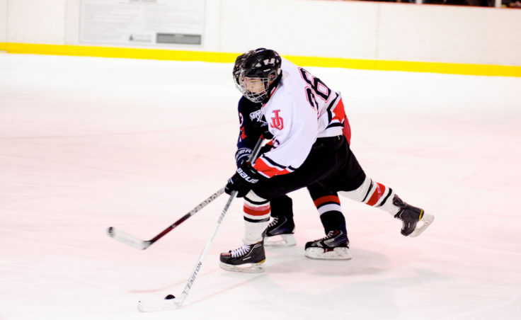 Juneau's Josh Lahnum gets tied up while skating toward North Pole goalie Allan Heineken.