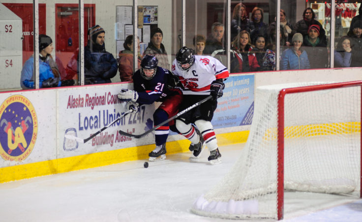 Juneau center Grant Ainsworth pins North Pole's James Laszoffy along the boards, looking to maintain possession of the puck during the two-game series at Treadwell Ice Arena.
