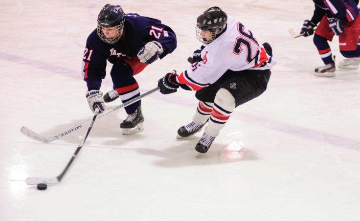 Juneau forward Josh Lahnum battles with North Pole's James Laszoffy for the puck during the two-game series at Treadwell Ice Arena.