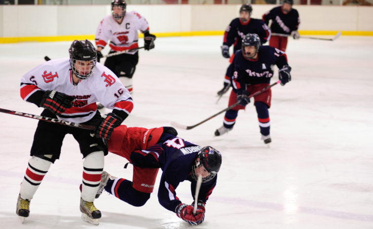 Juneau's Logan Moser puts the finishing touches on an open-ice check to North Pole's Wyatt Conrow during Saturday's game at Treadwell Ice Arena.