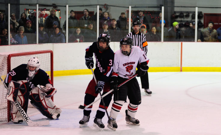Juneau forward Zach Easton battles for position in front of the net with North Pole's Carson Linnell.