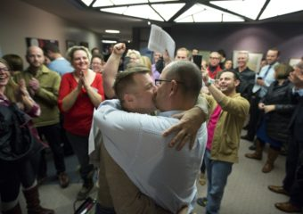 Chris Serrano, left, and Clifton Webb kiss after being married, as people wait in line to get licenses outside of the marriage division of the Salt Lake County Clerk's Office in Salt Lake City on Friday. Kim Raff/AP