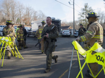 Connecticut State Police walk near the scene of the Sandy Hook Elementary School shooting on Dec. 14, 2012, in Newtown. Douglas Healey/Getty Images