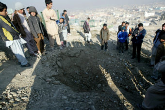 Afghans stand near a crater from an attack reportedly targeting the U.S. Embassy in Kabul on Wednesday. Ahmad Nazar/AP