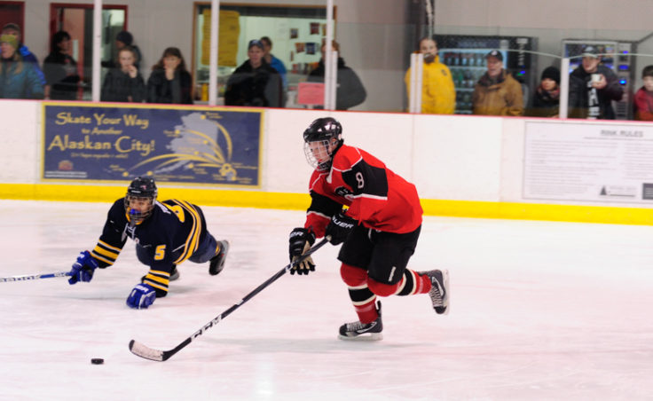 Juneau's Zach Hebert rushes in on Bartlett goalie Felix Malakye while skating past Bartlett's Raphael Turner during the weekend series at Treadwell Ice Arena.