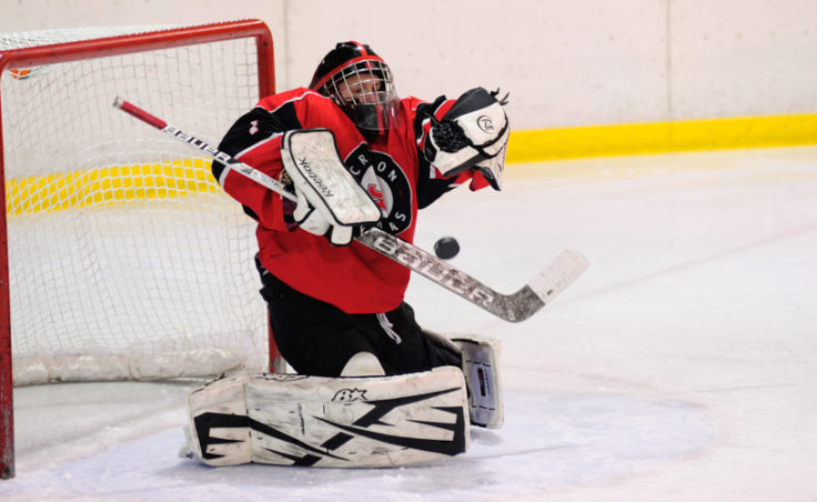 Juneau goalie Liam McDermott gets a blocker on a shot taken by a Bartlett skater during the weekend series at Treadwell Ice Arena.