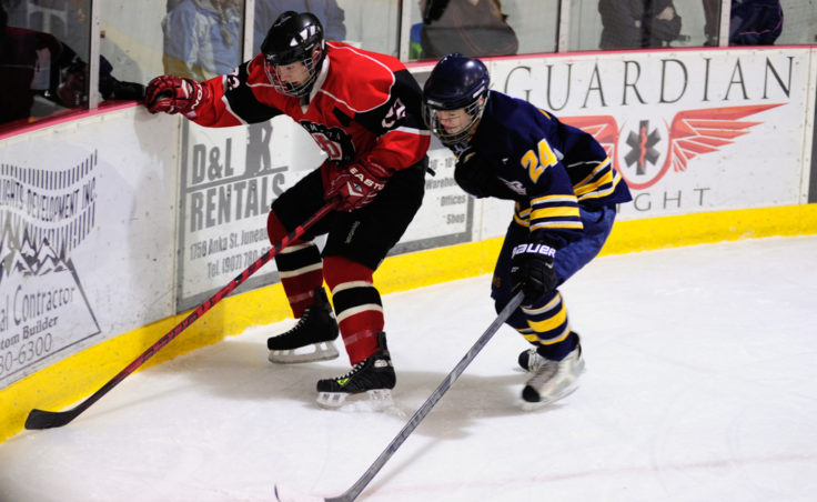 Juneau's Michael Dale tries to fend off Bartlett's Jordan Wallis along the boards during the weekend series at Treadwell Ice Arena.