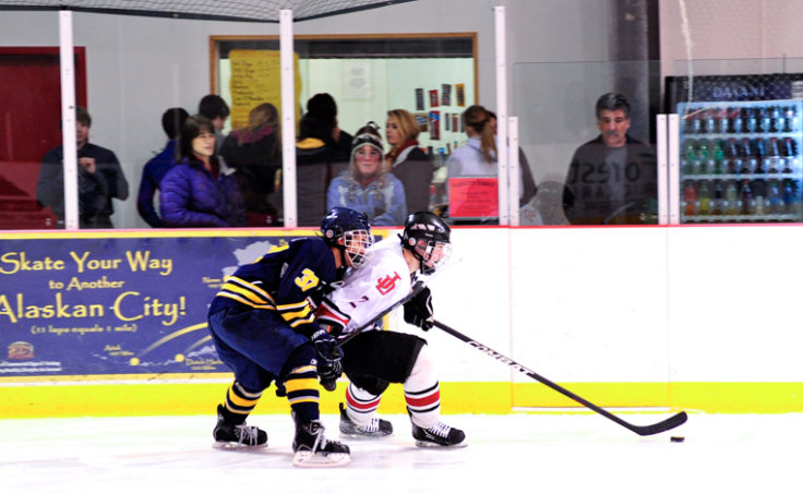 Juneau Captain Grant Ainsworth keeps Bartlett's Joel Johnson at bay while bringing the puck up ice from Juneau's defensive zone.