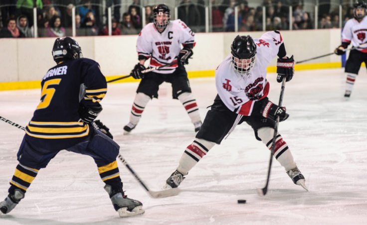 Juneau's Cole Cheeseman puts a move on Bartlett's Raphael Turner during the weekend series at Treadwell Ice Arena.