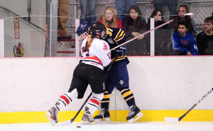 Juneau defenseman Kathryn Noreen pins Bartlett's Joel Johnson along the boards keeping her opponent away from the puck.