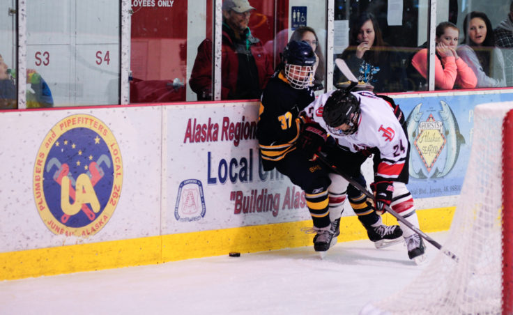 Juneau defenseman Chase Barnum knocks Bartlett's Joel Johnson off the puck during the weekend series at Treadwell Ice Arena.