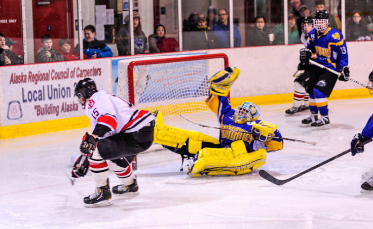 Juneau's Cole Cheeseman sends Monroe Catholic goalie Nathaniel Brose sprawling, but comes up short on this shot during the weekend series at Treadwell Ice Arena.