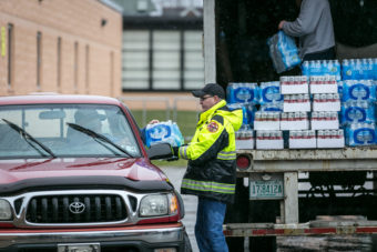 Members of the Nitro Volunteer Fire Department distribute water to local residents on Saturday. Michael Switzer/AP