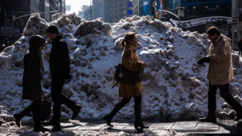 It will melt eventually: People walk past a pile of dirty snow in New York City's Times Square. Andrew Burton/Getty Images