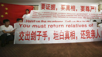 Newly arrived Chinese relatives of passengers of the missing Malaysia Airlines flight MH370 hold banners while talking to reporters at a hotel in Malaysia Sunday. The search continues for the jetliner that went missing three weeks ago. Aaron Favila/AP