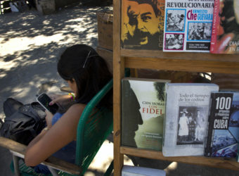 A book street vendor passes the time on her smart phone as she waits for customers in Havana, Cuba, on Tuesday. The Obama administration secretly financed a social network in Cuba to stir political unrest. Ramon Espinosa/AP