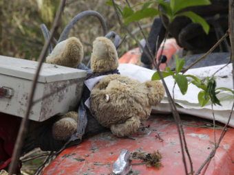 A stuffed bear sits with other items found nearby Wednesday atop a tractor that landed at the edge of the debris field in a deadly mudslide in Oso, Wash. Elaine Thompson/AP