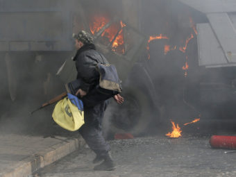 A man with a gun runs along a street during a clash between opposition protesters and riot police at a burning barricades near the Presidential office in Kiev, Ukraine, in February. Efrem Lukatsky/AP