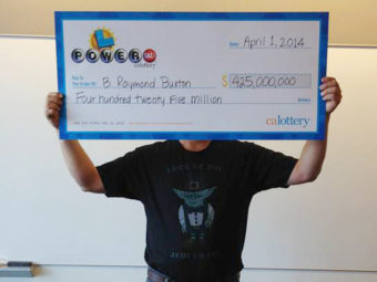 """Hidden, he is: This photo provided by the California Lottery shows Powerball winner B. Raymond Buxton holding his ceremonial check. The big winner is trying to keep his life private. He showed up in a T-shirt that says """"Luck of the Jedi, I Have."""" California Lottery/AP"""