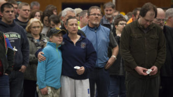 Gabriella Botamanenko (center left) hugs her mother, Angela Botamanenko, during a vigil for mudslide victims at the Darrington Community Center Saturday. A March 22 mudslide in a nearby community killed at least 30 and left many missing. David Ryder/Getty Images