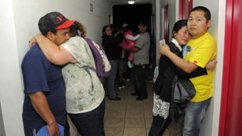 Scared residents hug in the hallway of an apartment building Tuesday after Iquique, Chile, was rocked by a strong earthquake. Cristian Viveros/AP