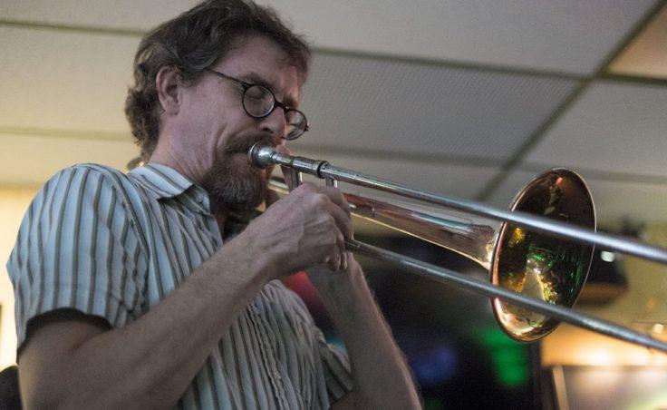 A man plays trombone in a bar