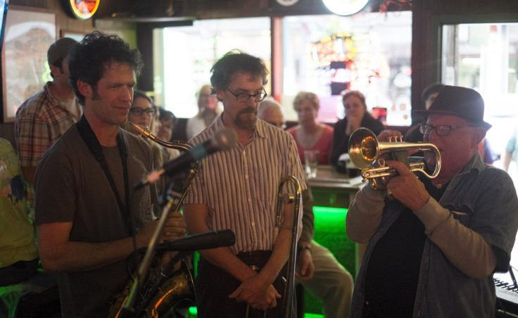 A man plays a cornet while two other men watch him in a bar