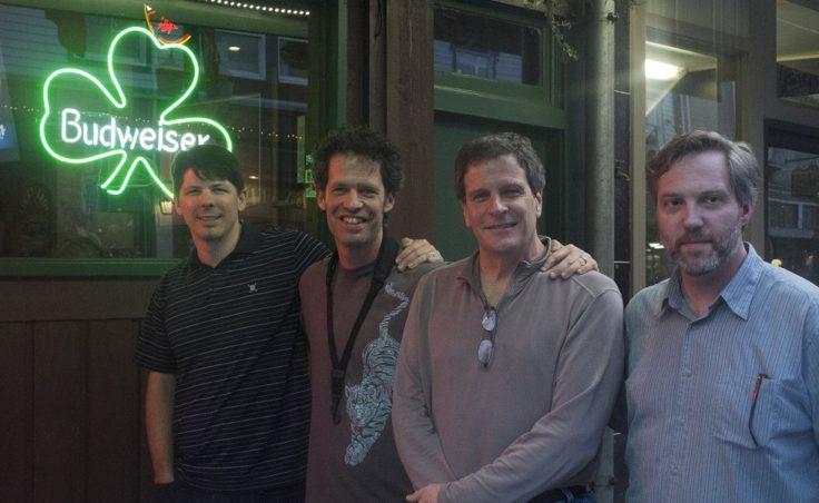 Four men stand outside an irish bar.