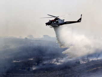 A helicopter attacks a wildfire burning in the north county of San Diego on Tuesday.AP