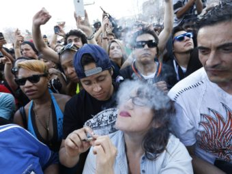 Partygoers listen to live music and smoke pot on the second of two days at the annual 4/20 marijuana festival in Denver, last month. While the sale of marijuana is legal in the state, a legal finance mechanism is still in doubt. Brennan Linsley/AP
