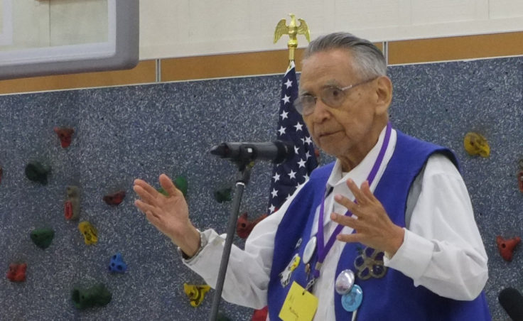 A man talking at a microphone in an elementary school