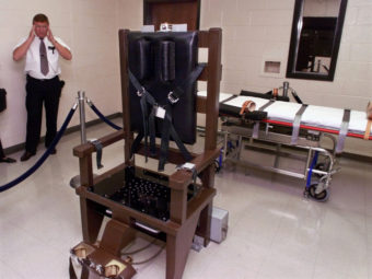A warden at Riverbend Maximum Security Institution in Nashville, Tenn., is shown in the prison's execution chamber in 1999. The electric chair is shown next to a lethal injection gurney. Mark Humphrey/AP