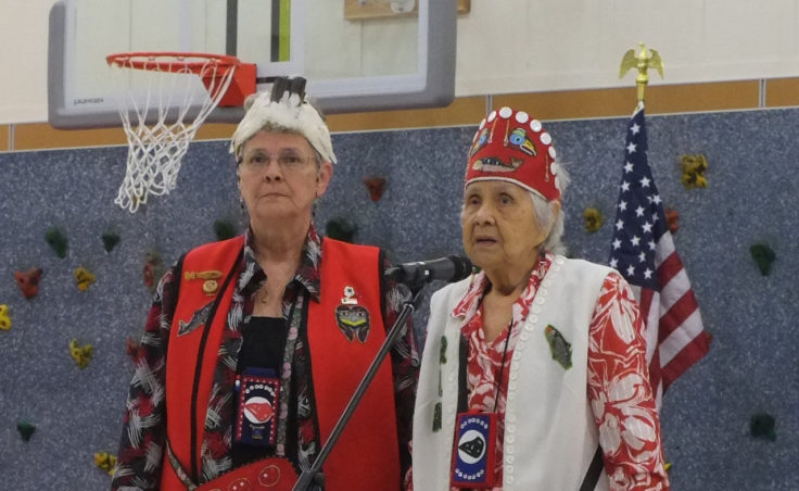 Two Tlingit women stand at microphone