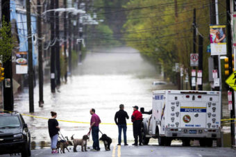 People gathered Thursday to view floodwaters from the Schuylkill River in Philadelphia. Much of the East and parts of the South have been hit by torrential rains. Florida's Panhandle and southern Alabama, for example, got about 2 feet of rain in 24 hours. Matt Rourke/AP