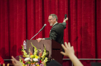 Retired teacher Clay Good kicked off his speech with a selfie from the stage. (Photo by Heather Bryant/KTOO)
