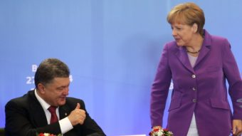 German Chancellor Angela Merkel speaks with Ukrainian President Petro Poroshenko, who signed a new economic deal with the EU at the organization's summit meetings Friday. Olivier Hoslet/AFP/Getty Images