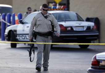 A Las Vegas police officer walks away from the scene of a shooting near a Wal-Mart on Sunday. John Locher/AP