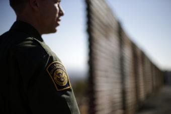 A Border Patrol agent looks to the north near where the border wall ends as it separates Tijuana, Mexico, (left) and San Diego. Gregory Bull/AP