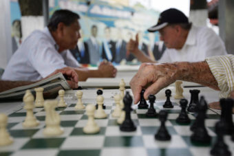 A elderly man makes a move on a chess board at the Maximo Gomez Domino park in Little Havana in Miami, where political opinions are shifting. Roberto Schmidt /AFP/Getty Images