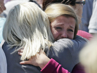 Freshman Hailee Siebert, 15, cries on her mother's shoulder after a shooting on Tuesday at Reynolds High School in Troutdale, Ore. The gunman has been identified as 15-year-old student Jared Michael Padgett. Rick Bowmer/AP