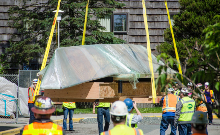 Construction crews hoisted the 45-foot walrus skin umiak up and over the Alaska State Museum with a crane. (Photo by Heather Bryant/KTOO)