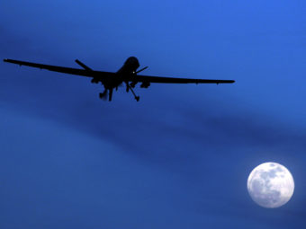 An unmanned U.S. Predator drone flies over Kandahar Air Field, southern Afghanistan, in 2010. A new report questions the U.S. policy of using armed drones abroad to carry out attacks on suspected terrorists. Kirsty Wigglesworth/AP