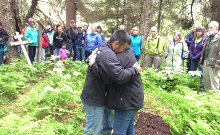 Martin Stepetin and wife Ann embrace when Martin breaks down in tears. Originally from St. Paul, Stepetin has family members who were interned in Funter Bay, 50 miles north of Killisnoo. (Photo by Lisa Phu/KTOO)