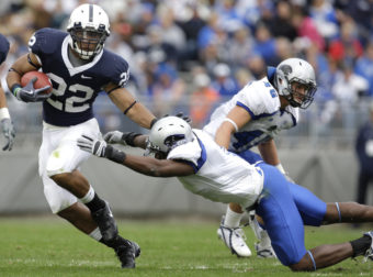 Penn State running back Evan Royster eludes a tackle by Eastern Illinois' Adrian Arrington during a 2009 NCAA college football game in State College, Pa. Arrington was one of the athletes who sued the NCAA over concussions. Carolyn Kaster/AP