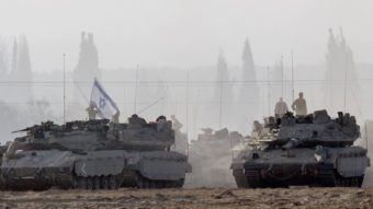 Israeli soldiers stand on their tanks near Israel's border with the Gaza Strip on Tuesday. Israeli warplanes pounded Gaza with more than 50 strikes overnight after Hamas militants fired scores of rockets over the border. Jack Guez/AFP/Getty Images