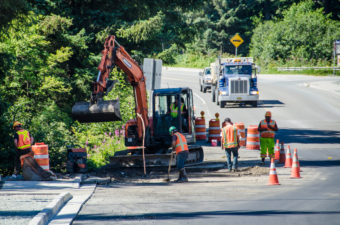 Crews finish construction around water pipe access points. (Photo by Heather Bryant/KTOO)