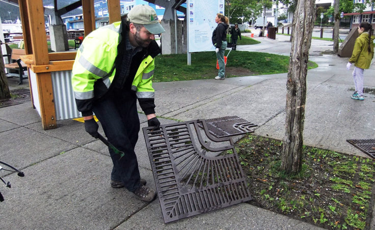 George Schaaf removes the grates from around the trees to clean up litter. (Photo by Rosemarie Alexander/KTOO)