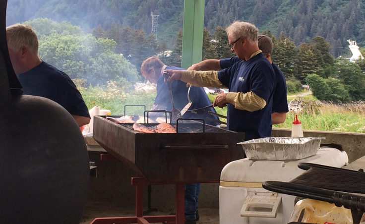 There was a dedicated grill team cooking hot dogs and salmon for picnic goers. (Photo by Sarah Yu/KTOO)