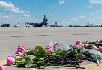 Flowers lay on the tarmac as a ground Hercules transport aircraft of the Royal Netherlands Air Force, carrying bodies from downed Malaysia Airlines Flight MH17, prepared to take off Wednesday in Kharkiv, Ukraine. Sergey Bobok /AFP/Getty Images